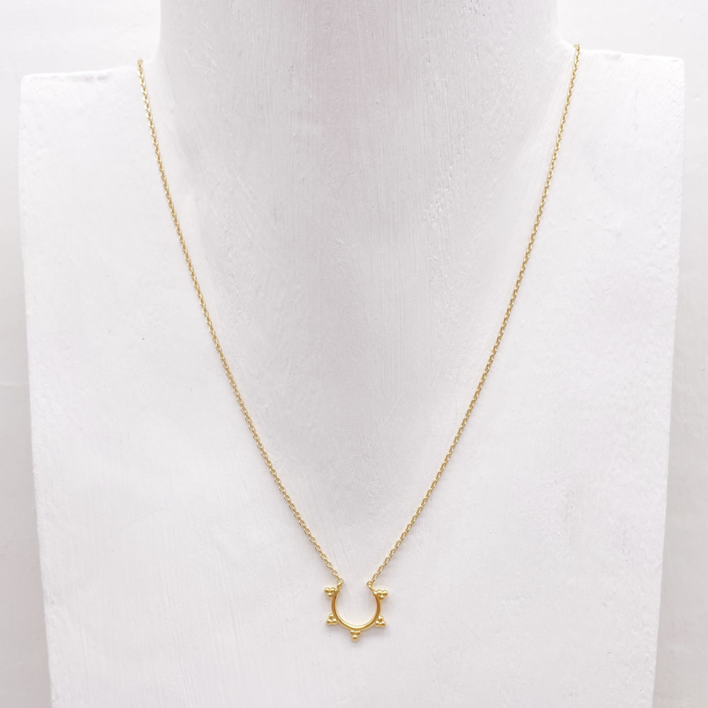 Golden semi-circle pendant necklace adorned with small dots